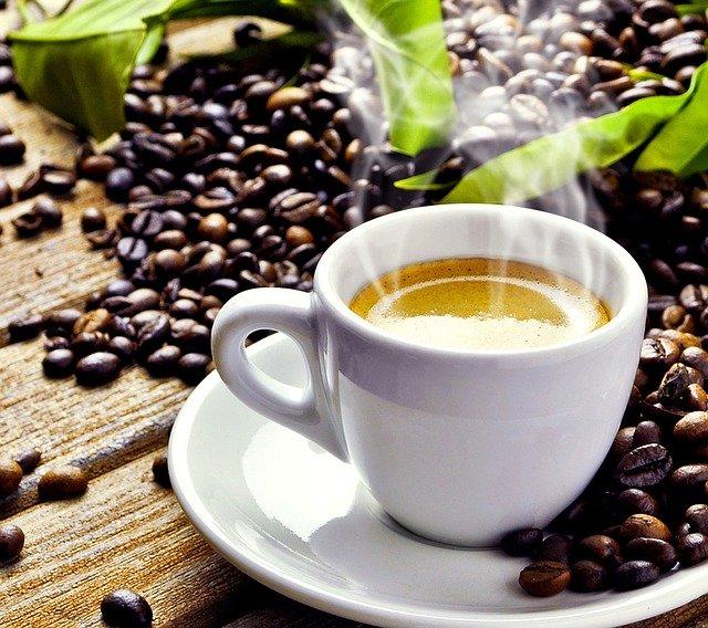 ホットコーヒーとそれを囲むコーヒー豆
