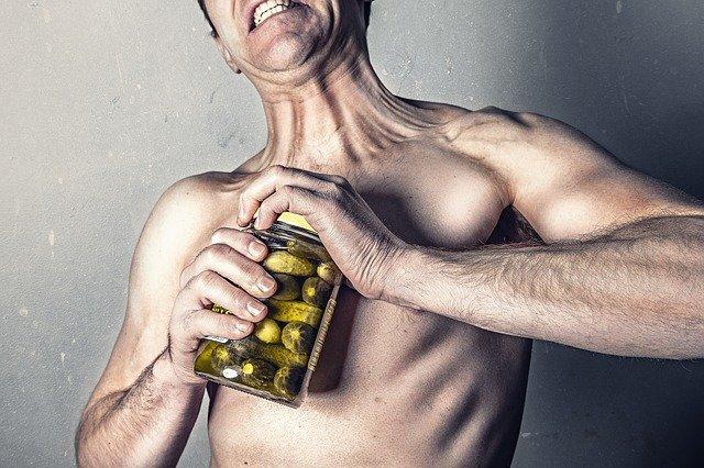 瓶のフタを力一杯開けようとする男性