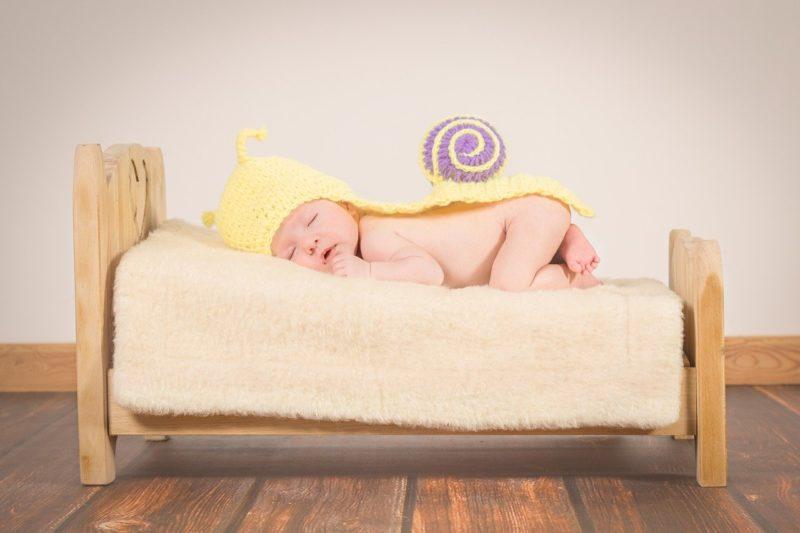 赤ちゃんがベッドの上でぐっすり眠っている画像